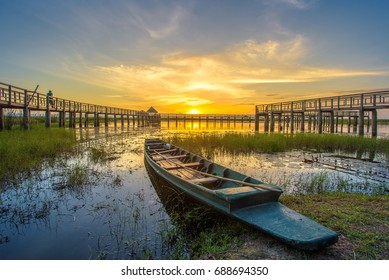 A beautiful golden sunset on the marsh. A row boat and a wooden bridge at the marsh at twilight. A man relaxing with the fantastic view of the golden sunset with the row boat.
