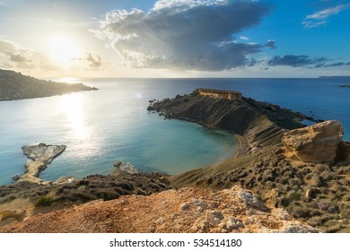 Beautiful golden Sunset over the blue of Gnejna Bay viewed from Ta Lippija, Mgarr, Malta
