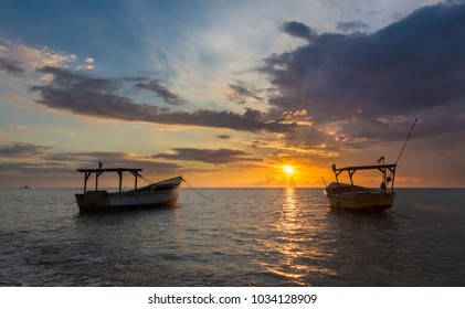 Beautiful golden sunset over the sea and fishing boats at the coast in Jamaica