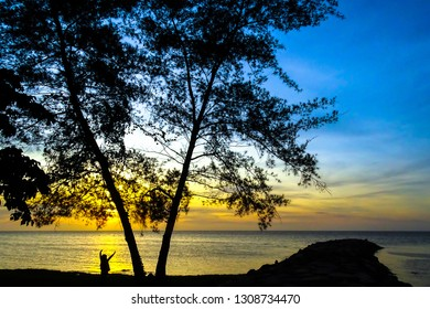 Beautiful golden sunset sandy beach and tropical trees with silhouette of a happy woman with hands raised in Labuan Pearl of Borneo,Malaysia.