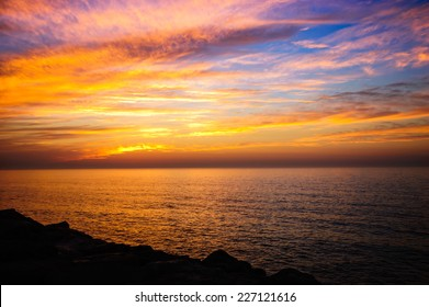 Beautiful golden sunset in the sea with saturated sky and clouds. Reflection in the water. Rocky coastal line. Peaceful serene landscape. Nature background.