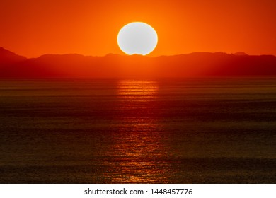 Beautiful golden sunset/sunrise over the sea behind mountains in background. Light reflection on the water as the sun sets/rises. Harmony and beauty in nature. Scenic peaceful ocean view.