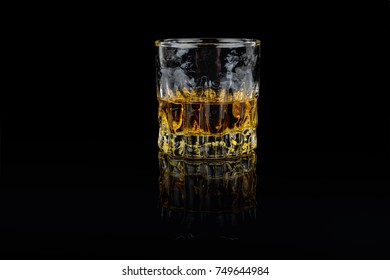 Beautiful golden tasty whiskey in a classic whiskey glass. Isolated studio shot on black background.