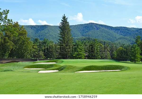 Ein schöner Golfplatz mit gepflegter Fairway und schöner Bergkulisse