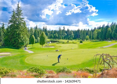 Beautiful golf course with a playing golfer in a sunny day with dark blue sky and clouds. Canada, Vancouver.