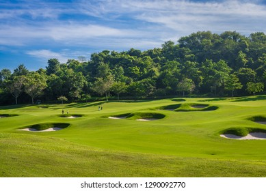 The beautiful golf course ,sand bunker and green grass with blue sky background.