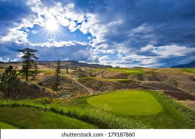 A beautiful golf course tee box with the sun peeking through the clouds