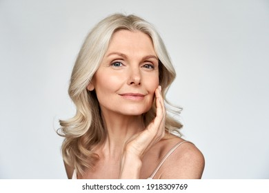 Beautiful gorgeous 50s mid aged mature woman looking at camera isolated on white. Mature old lady close up portrait. Healthy face skin care beauty, middle age skincare cosmetics, cosmetology concept