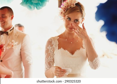 beautiful  gorgeous blonde bride crying  and stylish groom, hawai  colorful sand ceremony  on cyprus