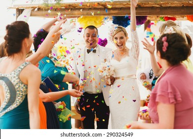 beautiful  gorgeous blonde bride  and stylish groom under confetti, hawai  colorful sand ceremony  on cyprus