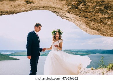 Beautiful gorgeous bride and stylish groom  on the cliff against sea