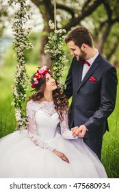 beautiful gorgeous brunette bride and stylish groom on the decorated swing on the tree