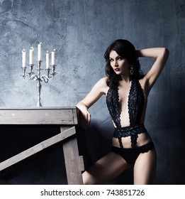 Beautiful, gorgeous and sexy woman posing in a fashion lingerie near a candlestick. Old ancient and shabby interior. Fashion, vogue and glamour concept.