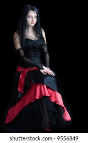 Beautiful gothic girl wearing vivid dress isolated on black