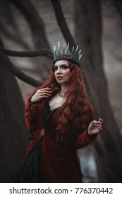 Beautiful gothic queen in red dress doing magic in the autumn forest