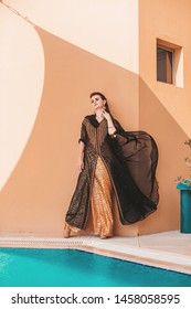 Beautiful graceful caucasian woman wearing abaya with the fabric streaming with  a wind
