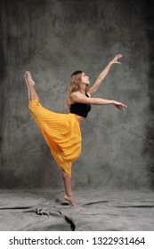 A beautiful graceful slender female dancer performs choreographic figures and movements on a gray dark fabric background. Concept of dance studio and choreography.