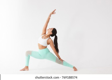 Beautiful graceful young woman in gymnastic costume doing pilates, yoga exercise or gymnastics for stretching hands and feet on white isolated background