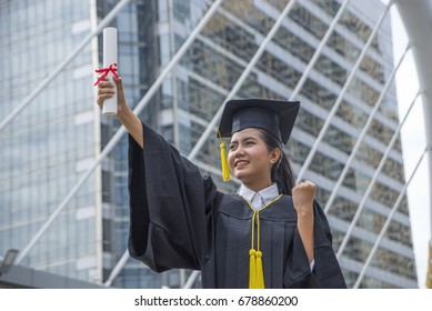 A beautiful graduate girl in the mantle keeps in hands graduation diploma