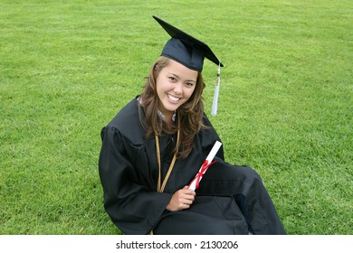 A beautiful graduate sitting on the lawn with diploma