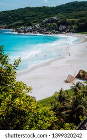 Beautiful Grand Anse beach with unrecognizable tourist people on La Digue island in Seychelles. Vertical shot