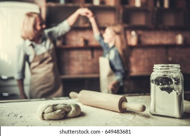 Beautiful grandma and granddaughter are dancing and smiling while baking in kitchen