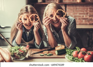 Beautiful grandma and granddaughter are holding slices of pepper, looking at camera and smiling while preparing salad in kitchen