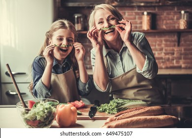 Beautiful grandma and granddaughter are making moustache of lettuce, looking at camera and laughing while preparing salad in kitchen