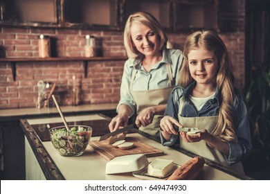 Beautiful grandma and granddaughter are making sandwiches, looking at camera and smiling while cooking in kitchen