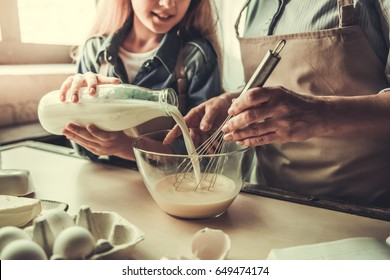 Beautiful grandma and granddaughter are whisking eggs, pouring milk and smiling while baking in kitchen