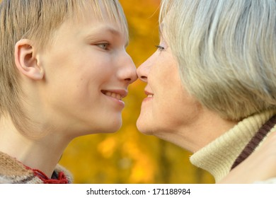 Beautiful grandmother with boy resting in the autumn park