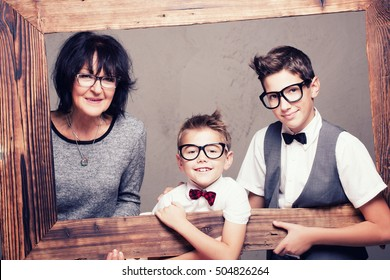 Beautiful grandmother posing with her grandchildren. Fashionable young boys smiling. Family portrait. Happiness.
