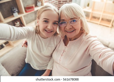 Beautiful granny and her granddaughter are doing selfie, looking at camera and smiling while sitting on couch at home