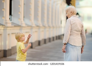 Beautiful granny and her little grandchild together walking. Grandma and grandson talking. Family communication concepts. Active longevity concepts.