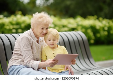Beautiful granny and her little grandchild together in park. Grandma and grandson seating on the bench and using tablet. Family communication concepts
