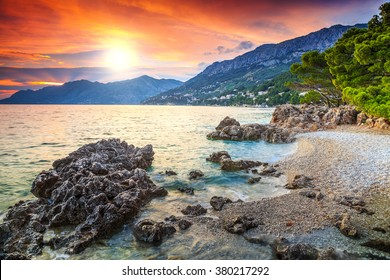 Beautiful gravel beach with Biokovo mountains on background and stunning colorful sunset,Brela,Makarska riviera,Dalmatia,Croatia,Europe