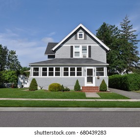 Beautiful gray suburban home gable style house blue sky clouds USA