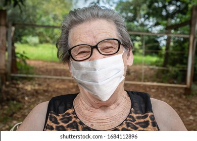Beautiful gray-haired old grandmother from the yard of the house in a medical mask with glasses and straightens the mask and looks. Covid-19. Coronavirus.