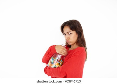 Beautiful greedy brown haired teenage girl of mixed race appearance holding tight big plastic jar with multicolored candies or jelly beans, about to eat everything by herself, not sharing with anyone