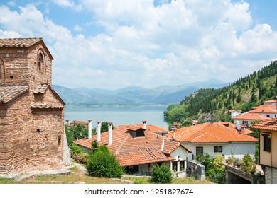 Beautiful greek landscape of mountain lake Orestiada with Kastoria roofs and old bysantine church. Greece, Kastoria.