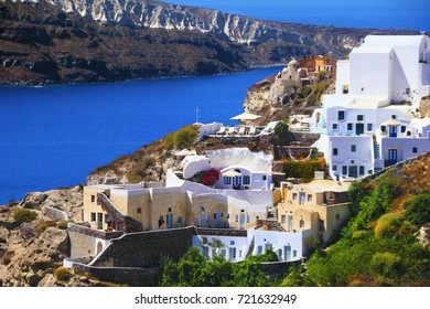 Beautiful greek scenery, traditional white cycladic architecture, chic hotels, sunbeds, foliage, black volcanic rocks and blue sea water in Oia village, Santorini island, Cyclades, Southern Greece