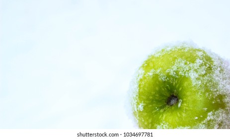 A beautiful green apple is scattered over white fluffy snow. Green apples on a white background. Close-up.