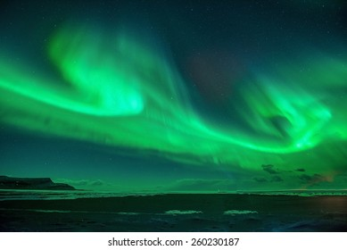 A beautiful green  aurora dancing over the Jokulsarlon lagoon, Iceland. northern lights over plane wreck  in Iceland.Contains Noise.