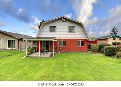 Beautiful green backyard with trimmed hedges, attached pergola with small patio area.