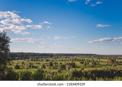 Beautiful green countryside landscape with charming calm blue sky with fluffy white clouds. Horizontal color photography.