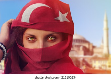 beautiful green eyed woman in national colored chador and the famous Hagia Sophia in Istanbul