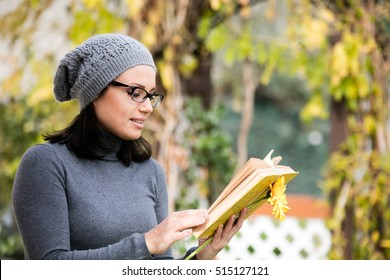 Beautiful green eyed young woman in warm clothes, vision glasses and gray hat smiling, reading a book and drinking tea outdoors in autumn time
