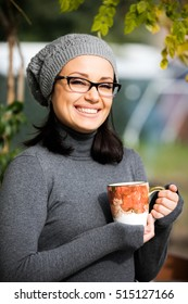 Beautiful green eyed young woman in warm clothes, vision glasses and gray hat smiling, drinking tea in a big cup outdoors in autumn time