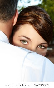 Beautiful green eyes of a bride looking over the grooms shoulder