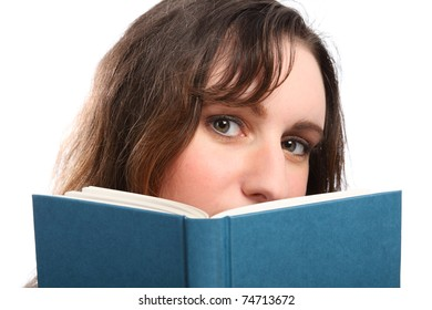Beautiful green eyes of young brunette woman looking up from behind a book she is reading.